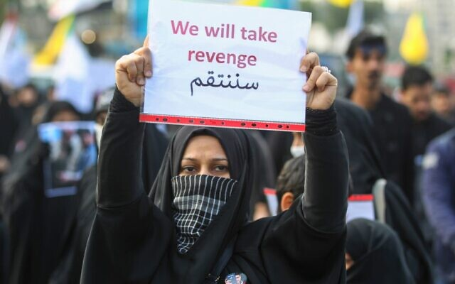 Iran threatens Tel Aviv, US bases in Middle East after killing of Soleimani:  An Iraqi woman holds a placard during the funeral of Iranian military commander Qasem Soleimani, Iraqi paramilitary chief Abu Mahdi al-Muhandis and eight others in Baghdad's district of al-Jadriya, in Baghdad's high-security Green Zone, on January 4, 2020. (Photo by AHMAD AL-RUBAYE / AFP)