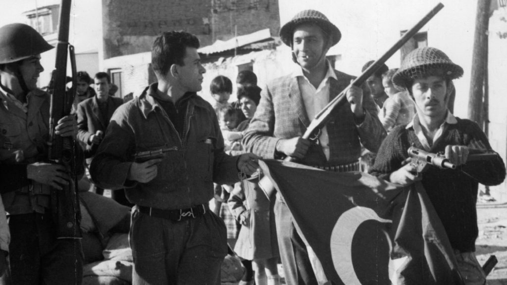 Circa 1974: Former EOKA terrorist Nikos Sampson leads armed men with a captured Turkish flag after a Greek Cypriot coup. He later declared himself President. (Photo by Keystone/Getty Images)