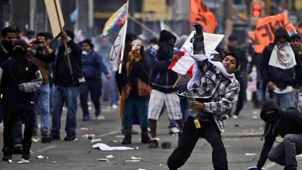 George Soros Behind The Protests In Peru To Destabilize The Region : Protester throwing some object