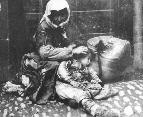 An Armenian woman and her child sit on a sidewalk next to a bundle of their possessions. Ottoman Empire - 1918-20   Armenian Genocide   NewsComWorld.com