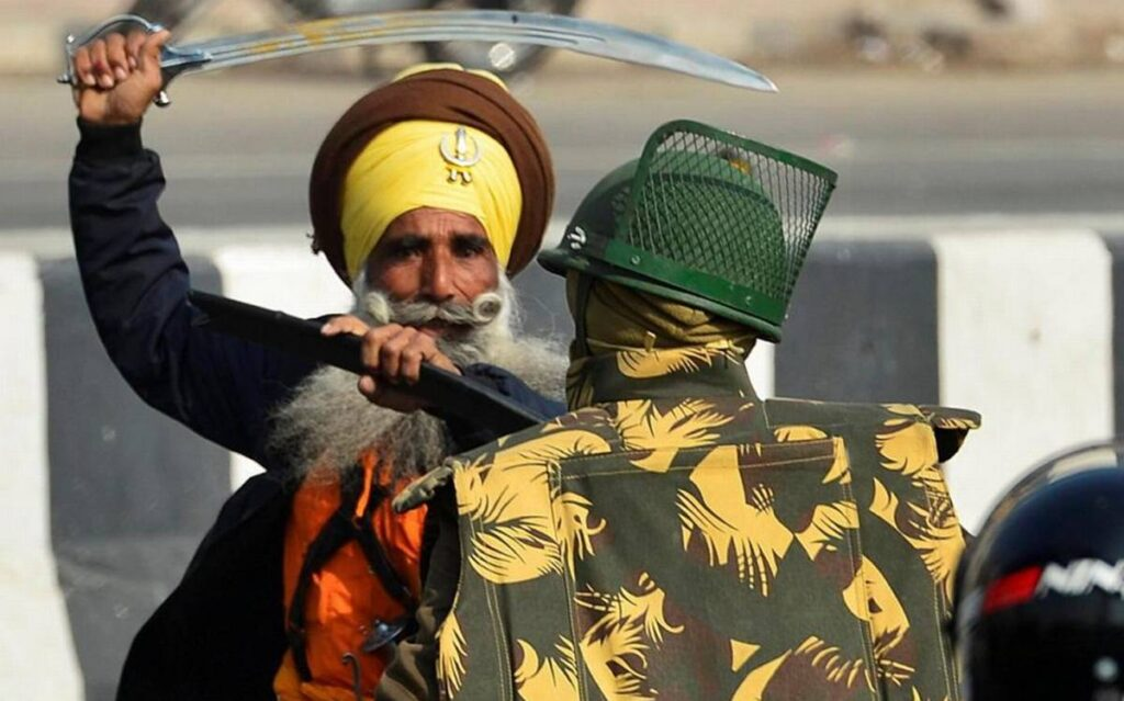 Khalistani Supporter attacking Police on duty with Sword during riots in New Delhi, India | NewsComWorld.com