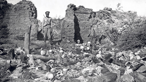 Turkish soldiers standing over the skulls of the Armenians murdered during Armenian Genocide.   Armenian Genocide   NewsComWorld.com